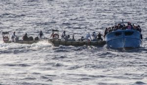 In this photo taken on July 2, 2013 and made available by the Italian Navy Wednesday, July 3, 2013, Coast Guard boats give help to a boat with some 80 migrants on a boat heading to Italy, in the Mediterranean sea, near the island of Lampedusa. The Vatican announced Monday that Pope Francis will go to Lampedusa island next week to meet with recently arrived migrants. Tens of thousands of clandestine migrants, many from Africa or the Mideast, head to Italian shores each year. Lampedusa is their frequent destination, closer to Africa than the Italian mainland. (AP Photo/Italian Navy, HO)
